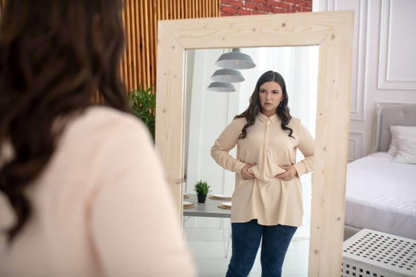 Mujer engordando mirándose al espejo
